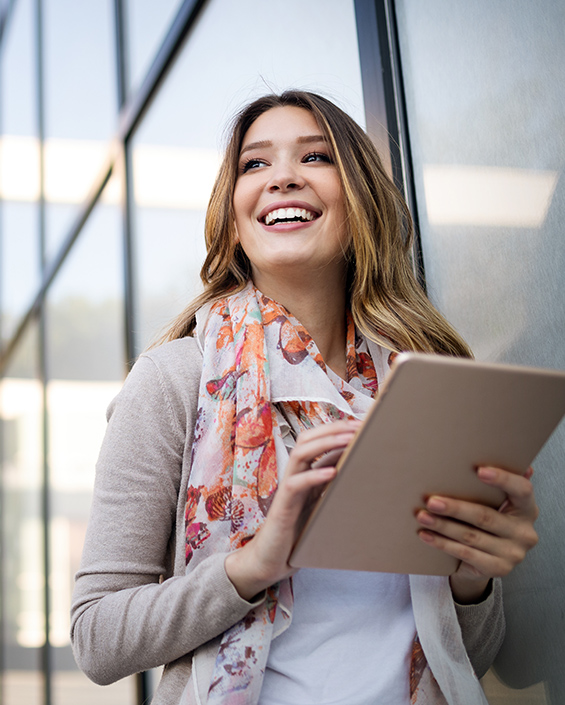 woman smiling holding ipad